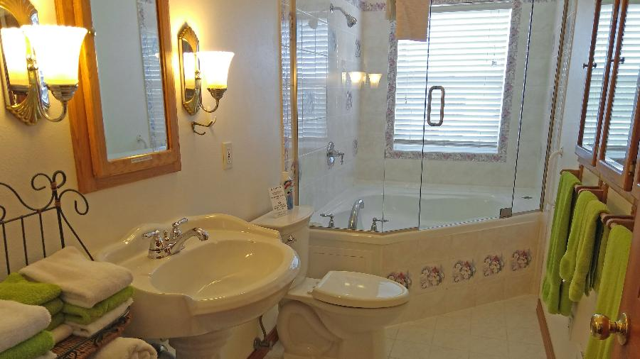 2nd-floor bathroom with shower and full tub?window has a west ocean view