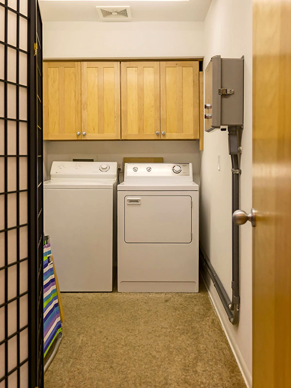 large laundry room with supplies just off entry from a shore walk
